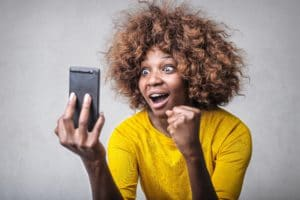 A woman looking at her phone, and getting very excited.